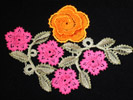 Rosalibre Lace, several pink flowers and an orange flower with white stems and leaves